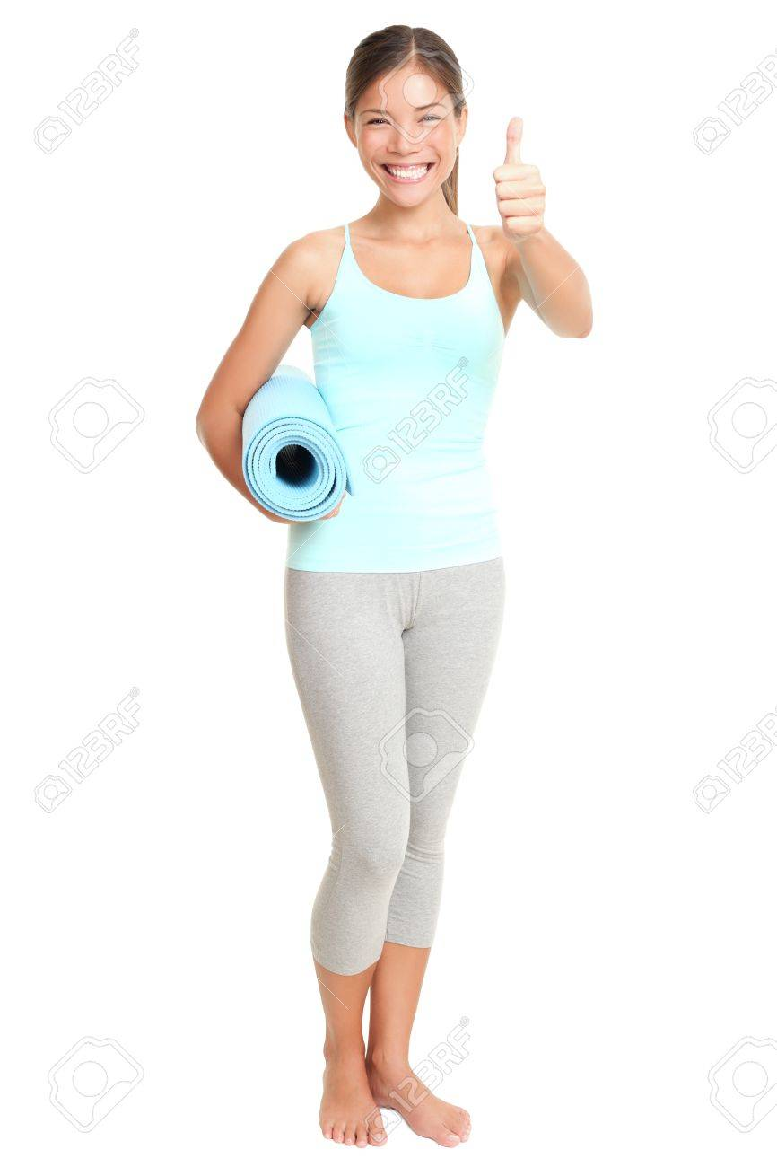 Fitness woman giving success thumbs up sign standing holding exercise yoga mat. Young sporty fit mixed race Asian / Caucasian female model isolated on white background in full body. Stock Photo - 9152608