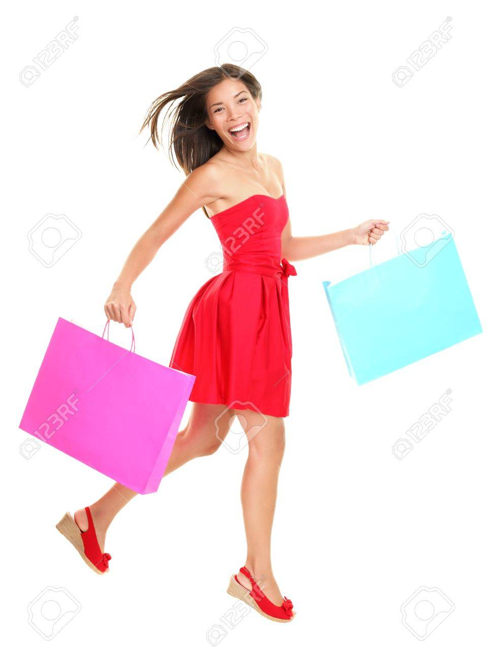 Shopper - woman shopping holding shopping bags in red summer dress. Young asian woman walking cheerful and smiling isolated in full body on white background. Mixed race Asian / Caucasian female model. Stock Photo - 9607536