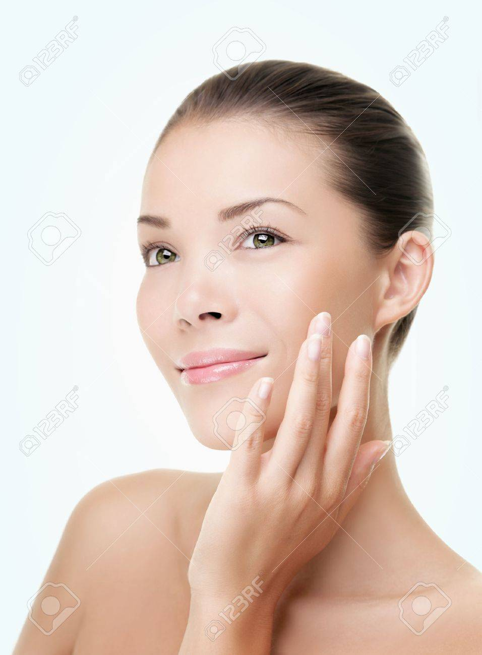 Skin care beauty woman. Beauty woman smiling applying cream. Beauty portrait of beautiful Asian / Caucasian female model isolated on light blue background looking at copy space. Stock Photo - 9952938