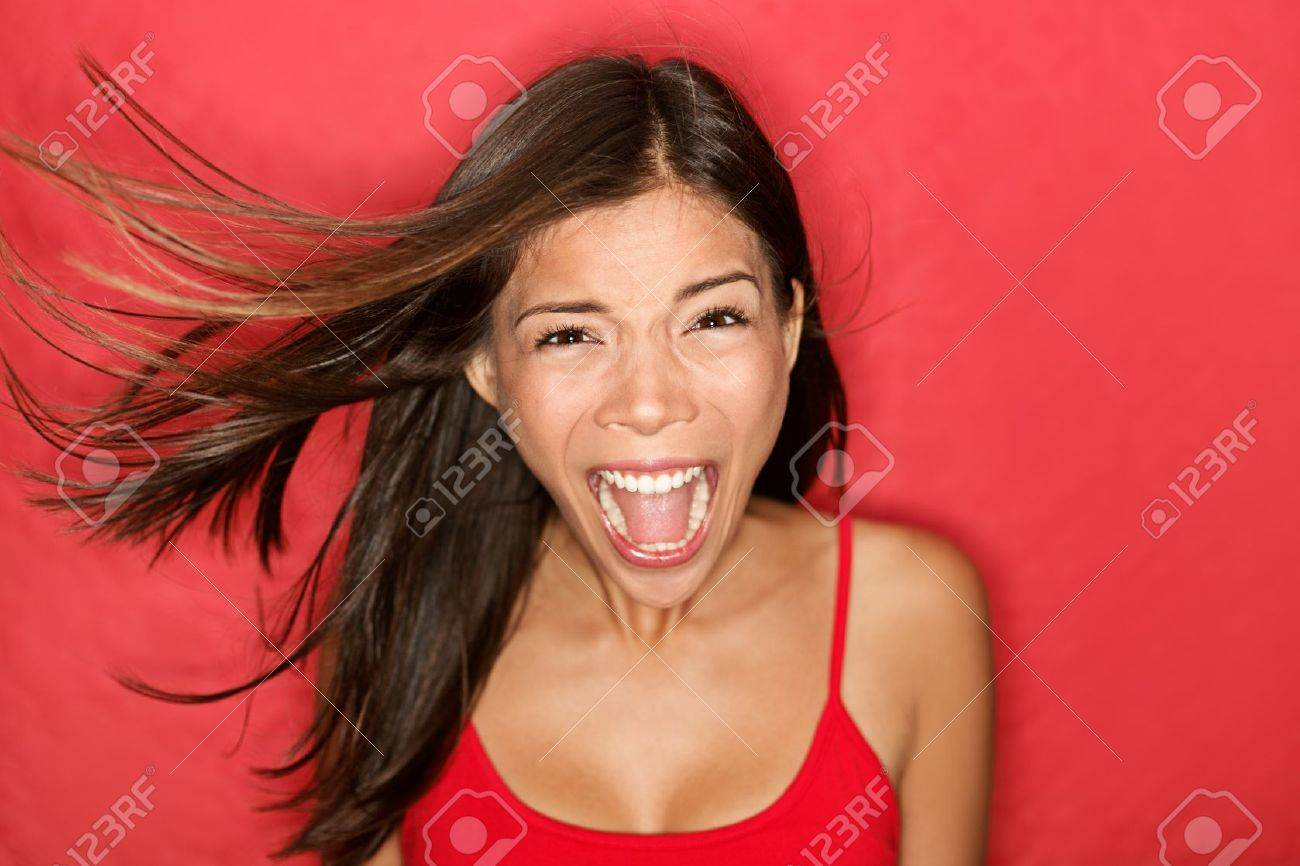 Scream. Woman screaming wild and crazy at full energy looking at camera on red background. Beautiful mixed race Asian Caucasian brunette female model with wind in the hair. Stock Photo - 10043822
