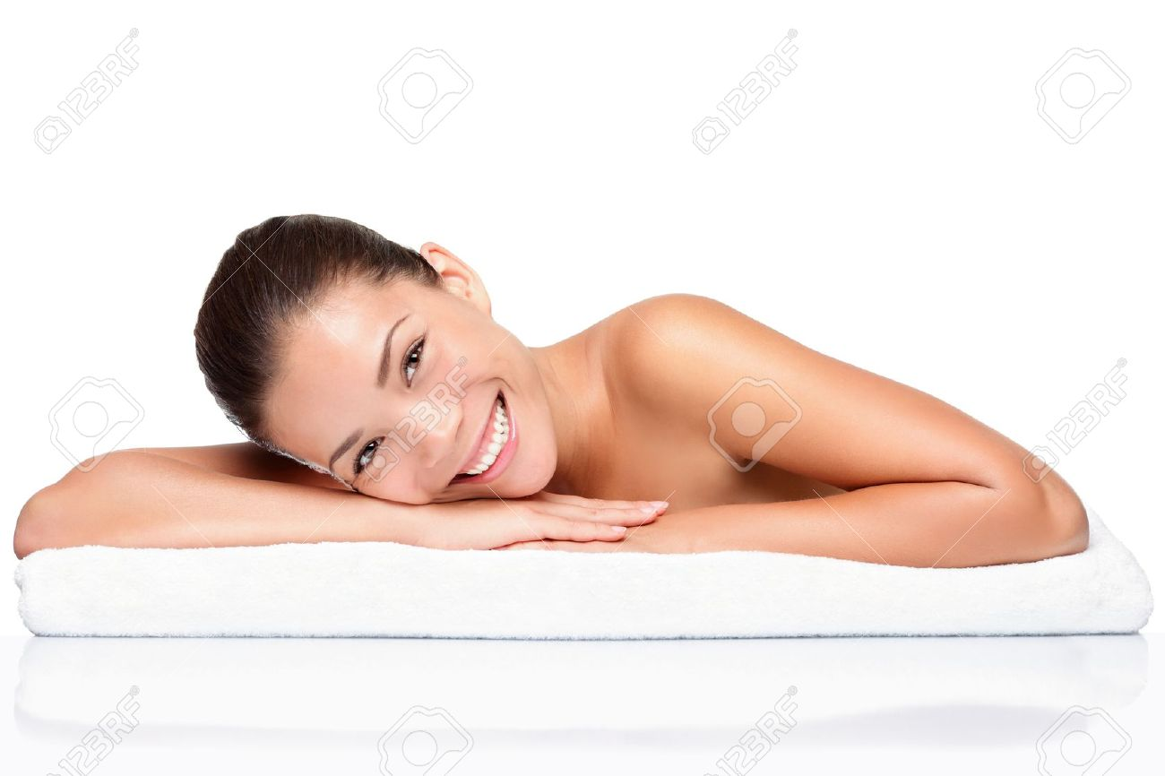 Spa. Face skincare beauty woman smiling happy. Portrait of beautiful attractive mixed race Chinese Asian / Caucasian female model lying down on towel during skin care treatment. Girl isolated on white background. Stock Photo - 10043842