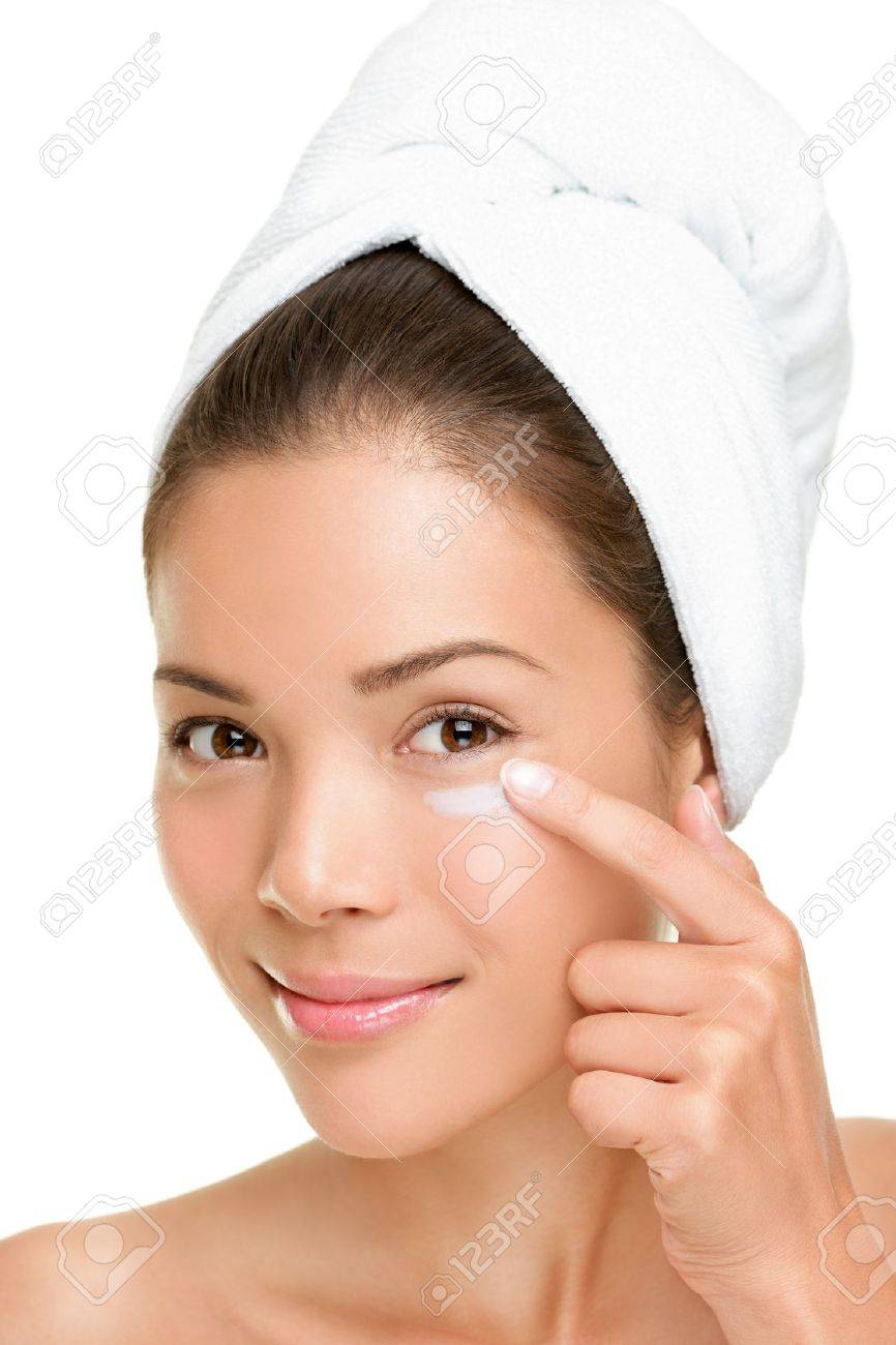 Skin care woman putting face cream touching under eyes. Facial beauty closeup of beautiful mixed race Asian / Caucasian female model isolated on white background. Stock Photo - 10097664