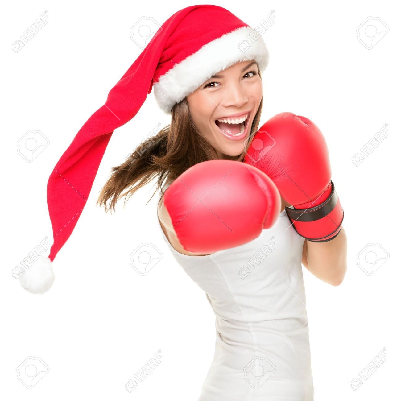 Christmas woman hitting wearing boxing gloves and red santa hat. Shopping boxing day or fitness concept. Beautiful fresh energy from asian caucasian female model isolated on white background. Stock Photo - 10914919