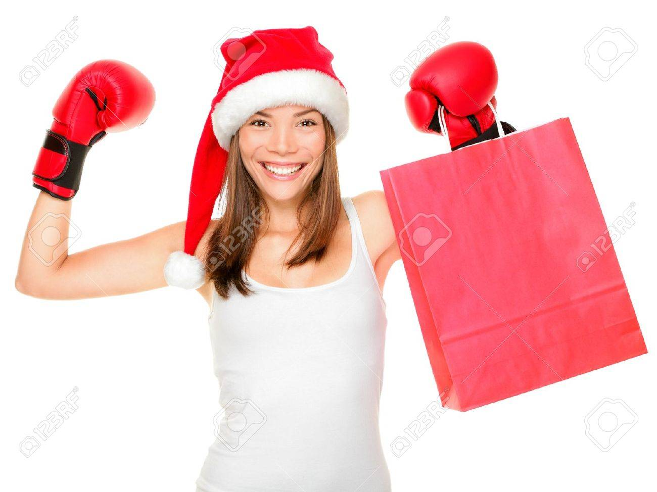 Christmas shopping boxing day concept with woman holding shopping bag wearing santa hat and boxing gloves. Funny fresh image of beautiful mixed race Asian Caucasian female model isolated on white background. Stock Photo - 10914490