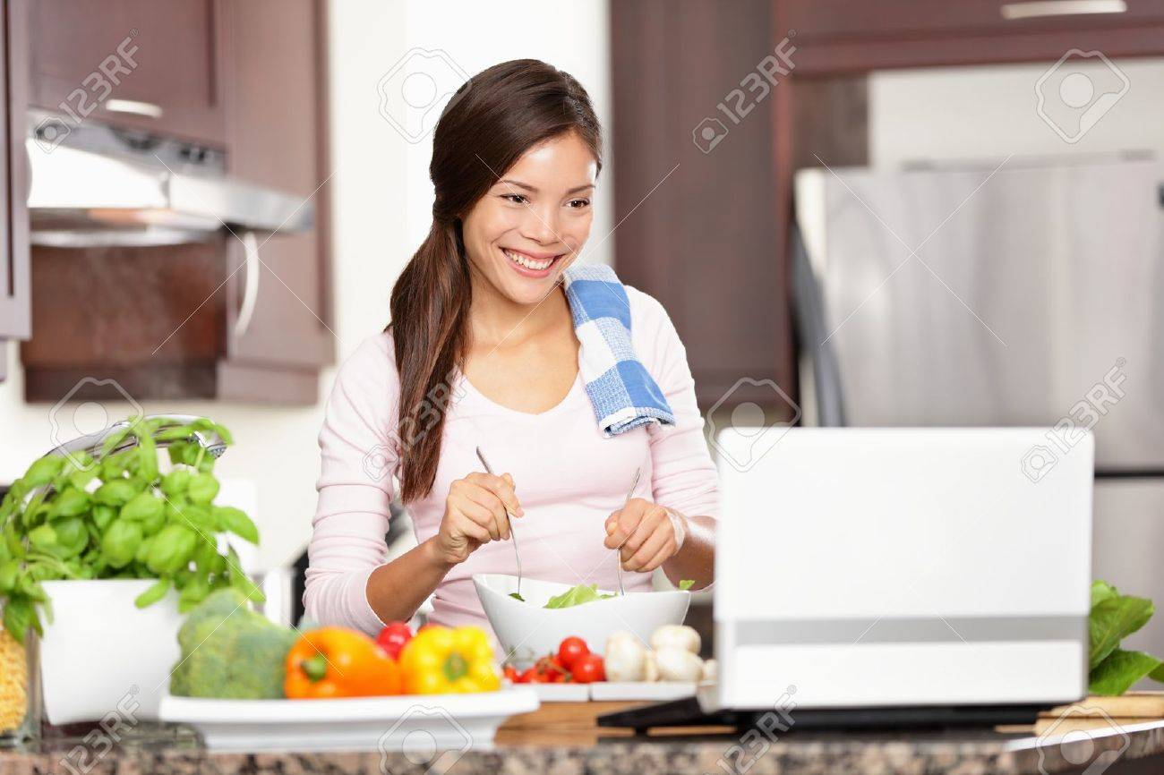 Cooking woman looking at computer while preparing food in kitchen. Beautiful young multiracial woman reading cooking recipe or watching show while making salad. Stock Photo - 10995386
