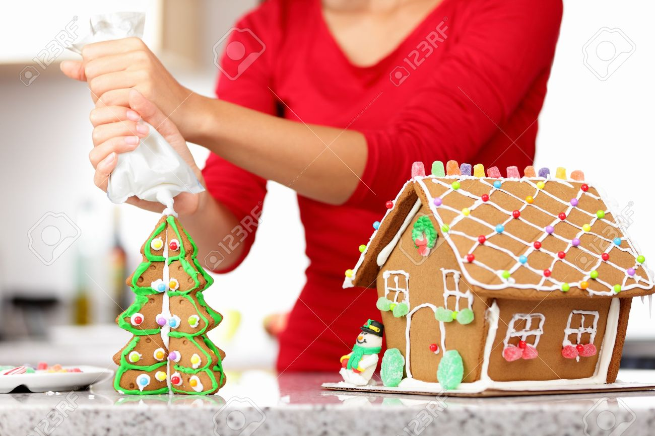 gingerbread house. Woman in holidays preparations putting glazing on gingerbread house Christmas trees. Stock Photo - 10995397