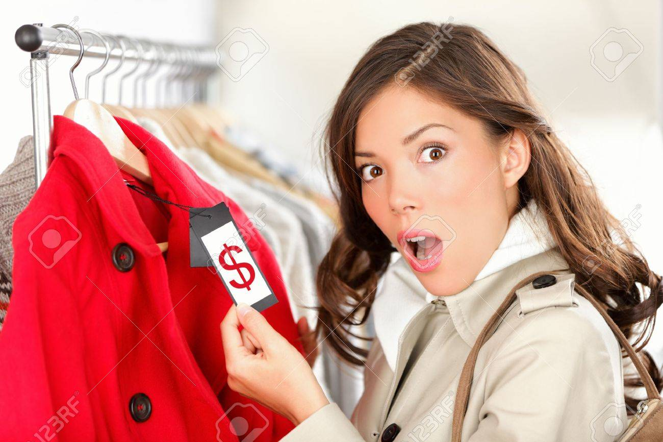 shopping woman shocked and surprised over price looking at price tag on coat or jacket. Woman shopper shopping for clothes inside in clothing store. Funny image of Asian / Caucasian female model. Stock Photo - 11155123