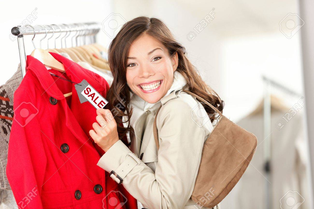 Shopping woman excited showing price tag at clothes sale in clothing store. Smiling cheerful woman. Price label reads sale. Stock Photo - 11155124