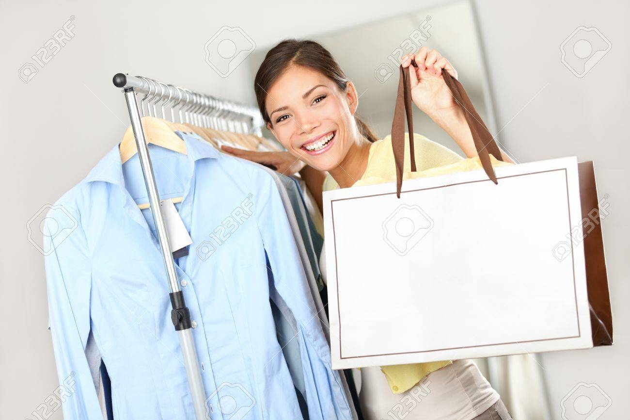 Shopper woman showing shopping bag sign with copy space for text. Woman standing by clothes rack in clothing store. Happy smiling multiracial Caucasian / Asian female model. Stock Photo - 11162211