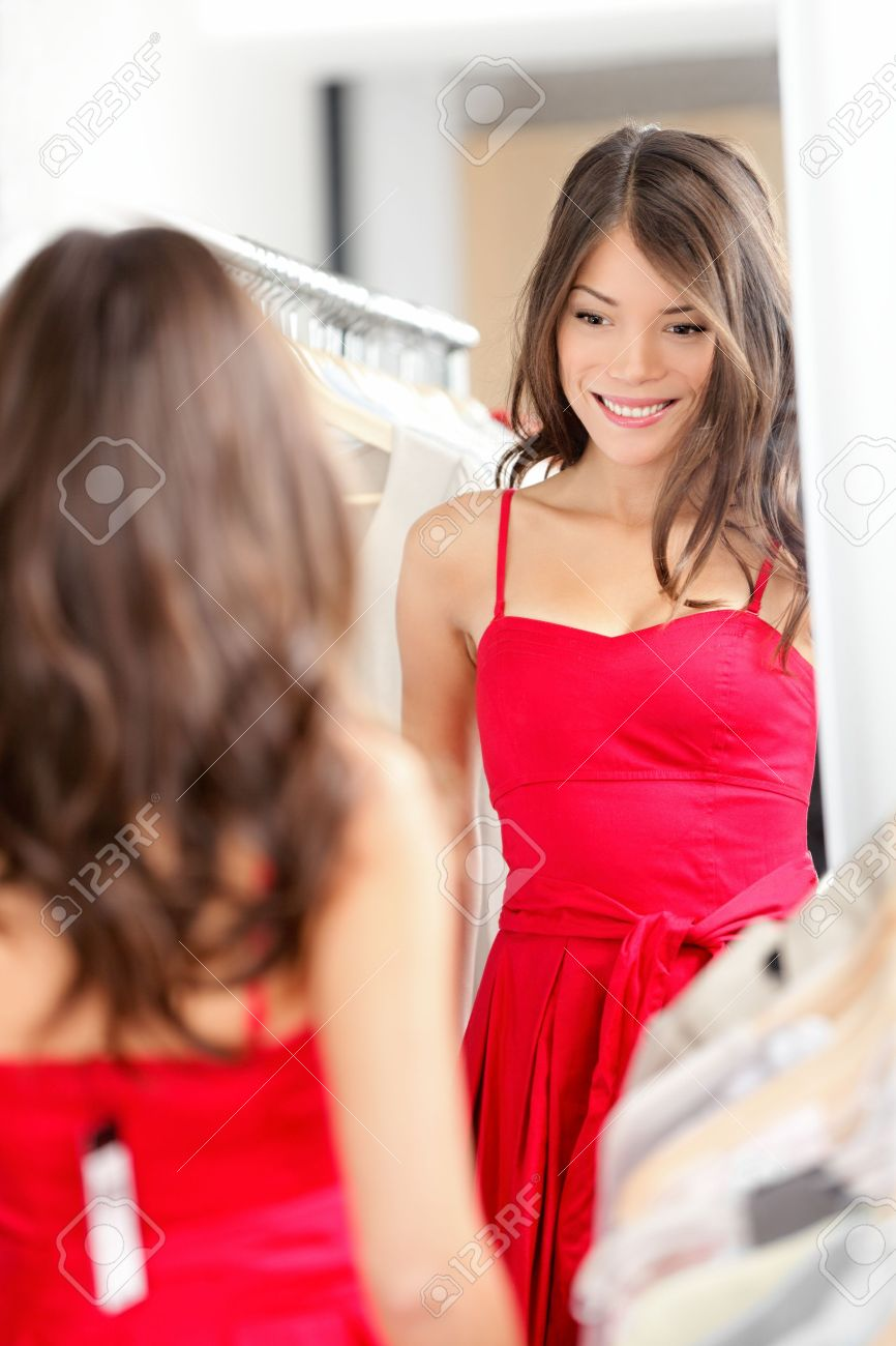 e04169835d0 Woman trying on dress clothes. Beautiful young woman in clothing store  looking at mirror buying new red dress. Gorgeous mixed race Caucasian    Chinese Asian ...