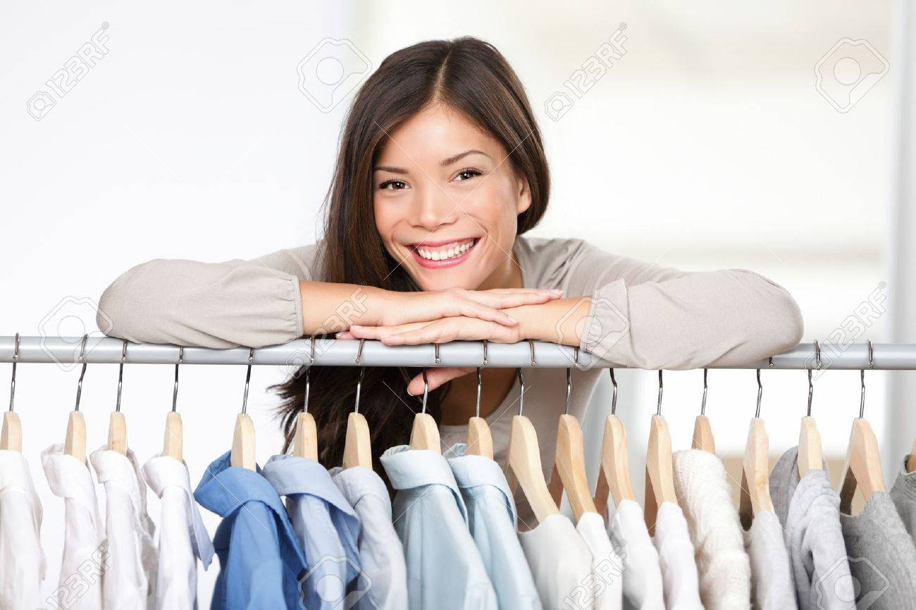 Business owner - clothes store. Young female business owner in her shop behind clothes rack smiling proud and happy. Multicultural Caucasian / Asian female model. Stock Photo - 11286038