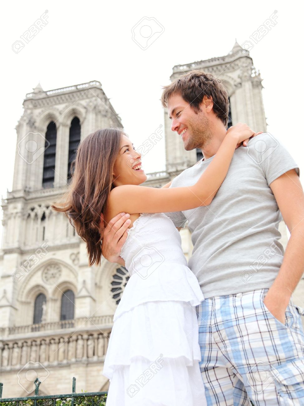 Notre Dame de Paris. Happy young couple in front of Notre Dame Cathedral in Paris, France. Asian woman and Caucasian man. Stock Photo - 11888213
