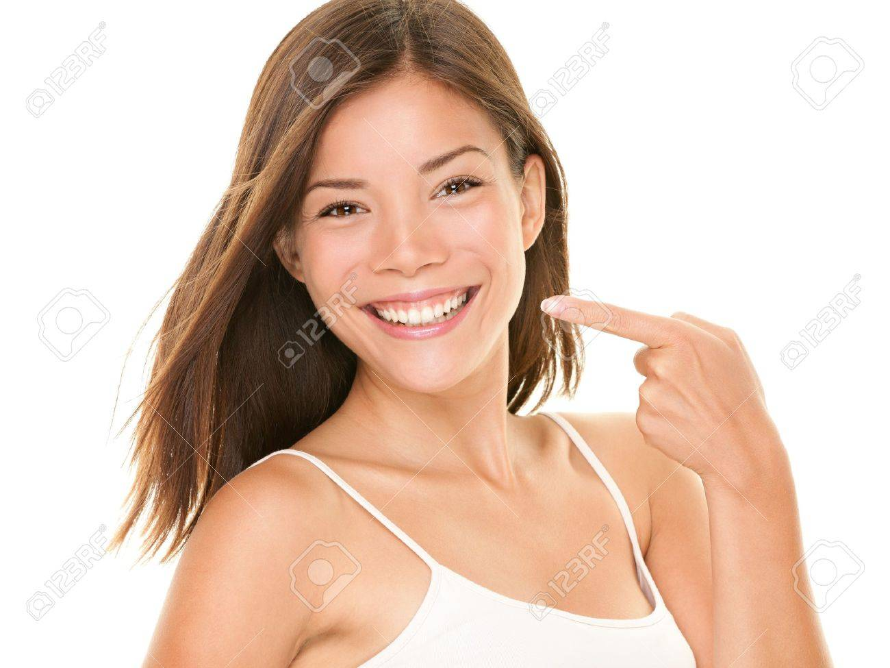 Dental teeth - perfect smile woman pointing at toothy smile looking happy at camera. Standard-Bild - 12344076
