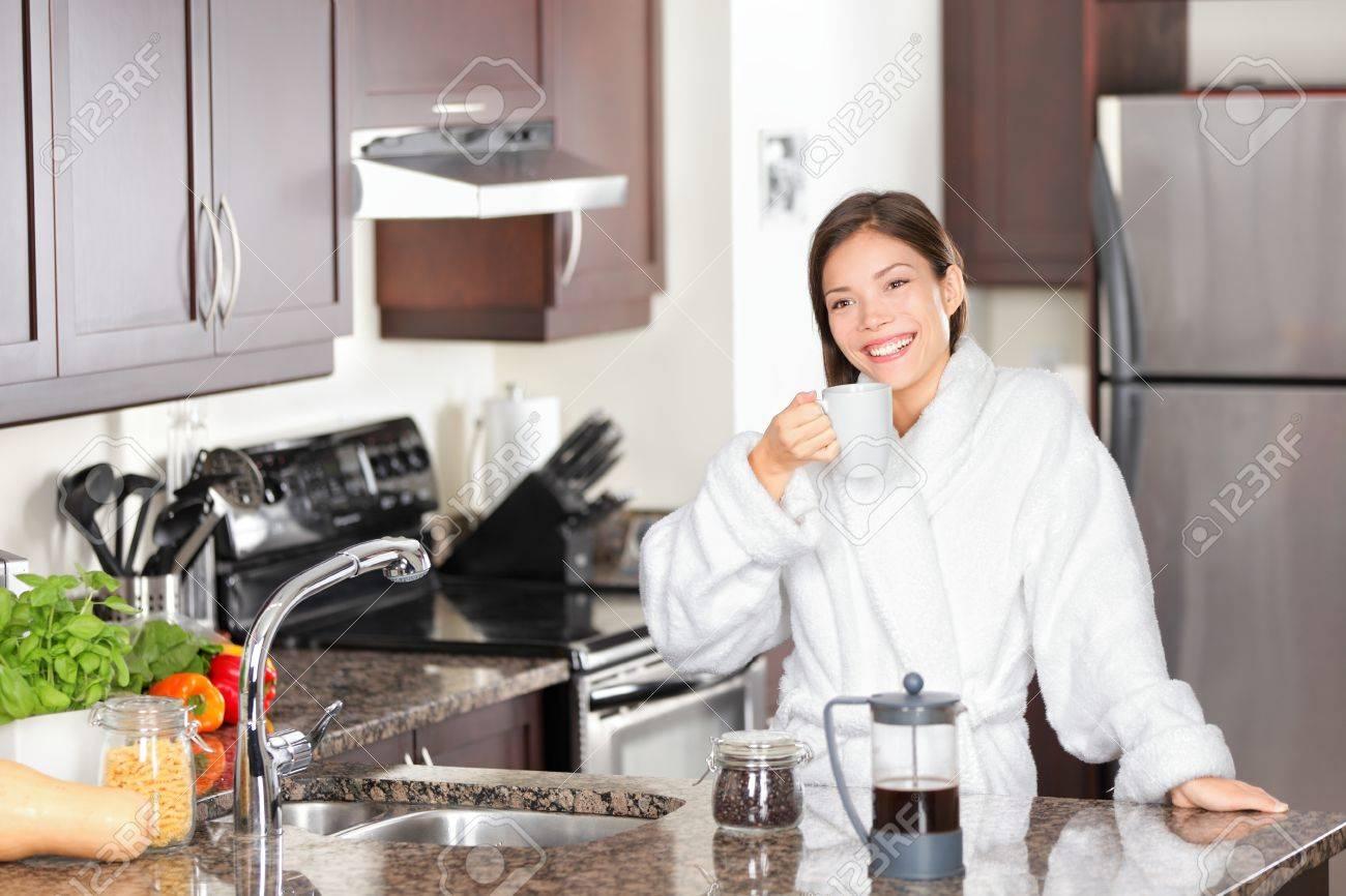 Mujer Bebiendo Café De La Mañana De Pie En La Cocina Casual En Bata ...