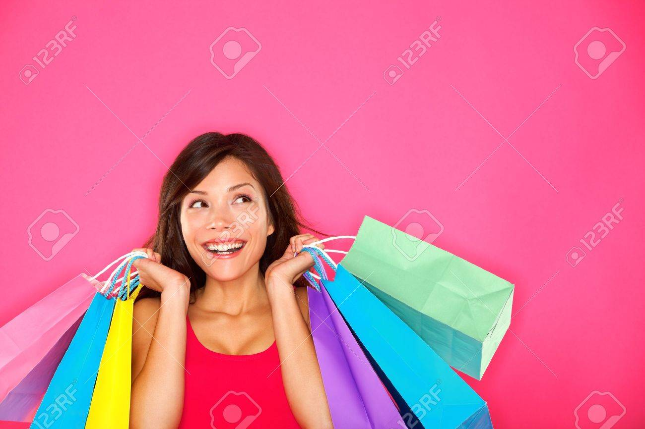 Shopping woman holding shopping bags looking up to the side on pink background at copy space. Beautiful young mixed race Caucasian / Chinese Asian shopper smiling happy. Stock Photo - 12935364