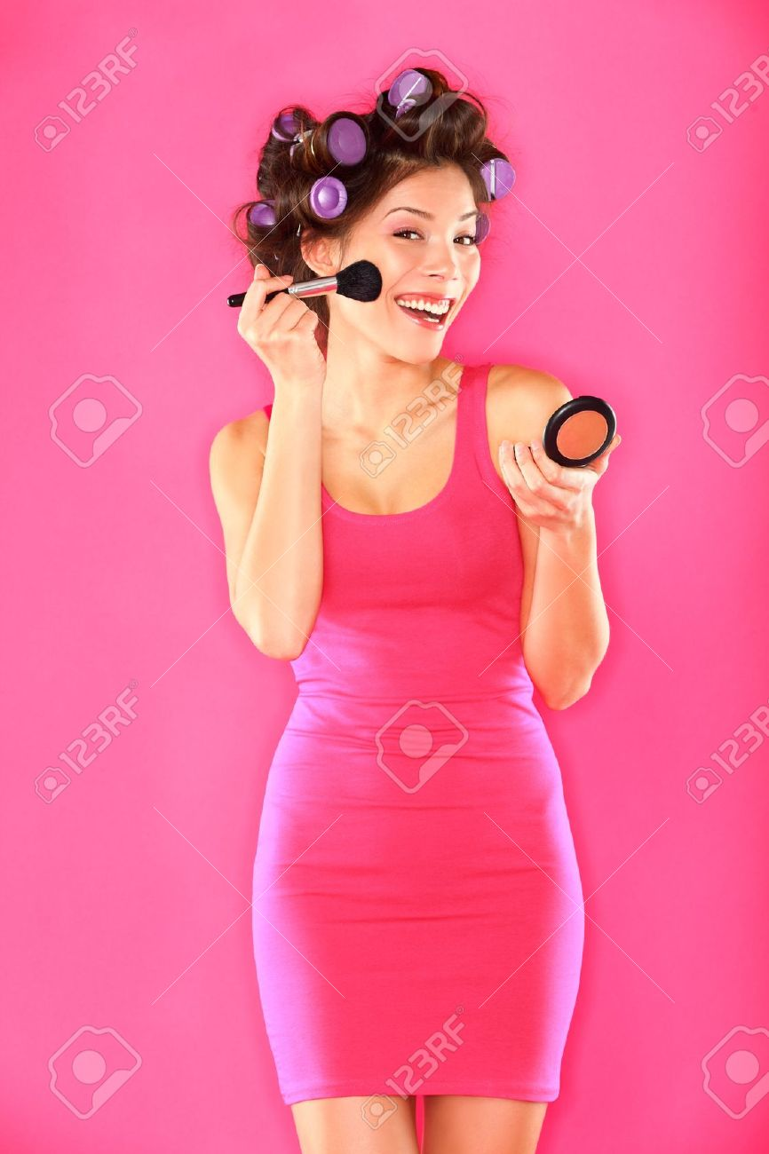 Woman putting makeup getting ready for fun  Funny image of beautiful young female model with hair rollers in pink dress on pink background  Funky trendy young multicultural Caucasian   Asian girl brunette Stock Photo - 13101081