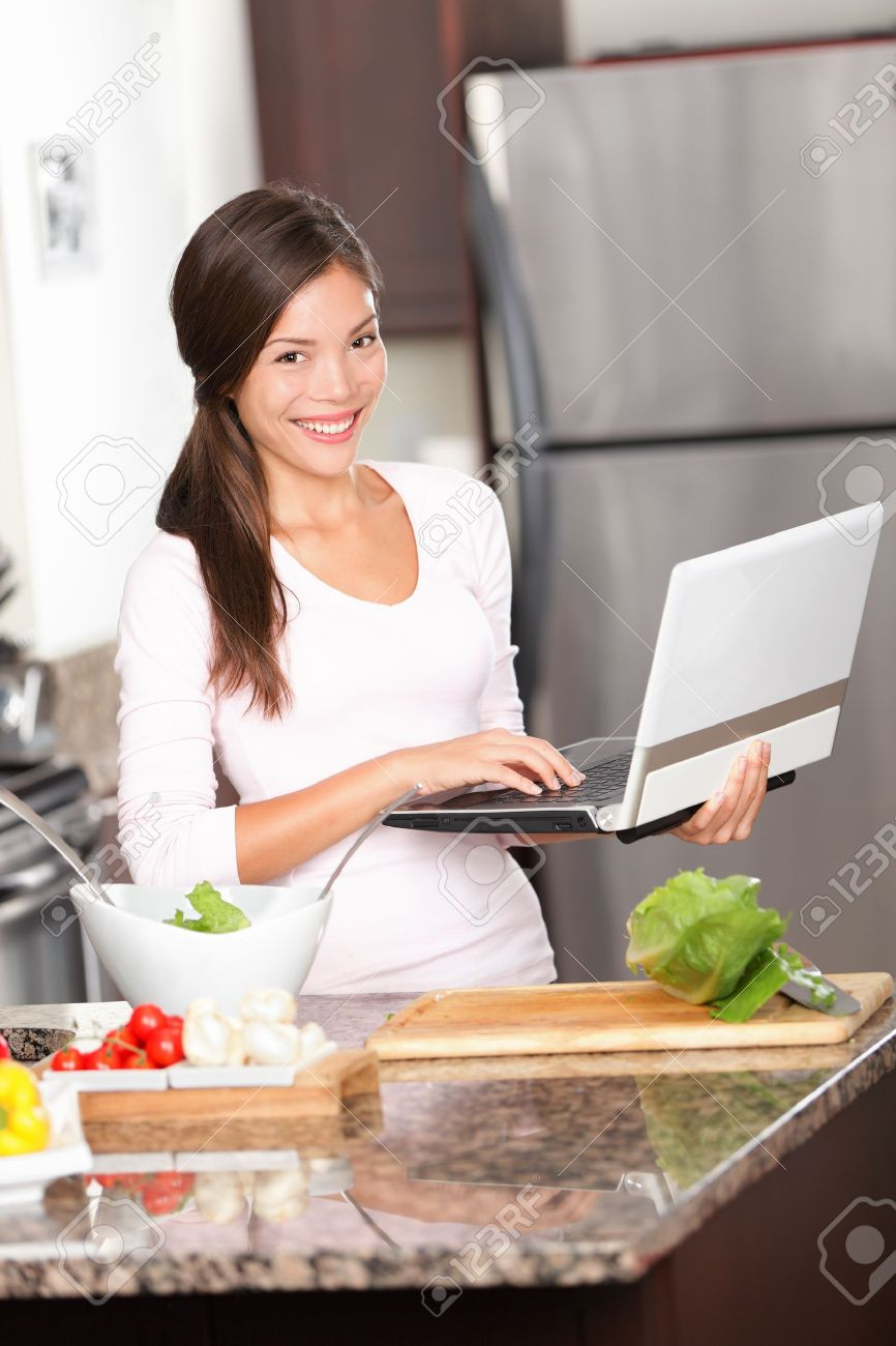 Kitchen woman on laptop PC cooking making food using computer for recipes etc  Beautiful young modern lifestyle image of multiracial Caucasian   Chinese asian young woman at home Stock Photo - 13259705