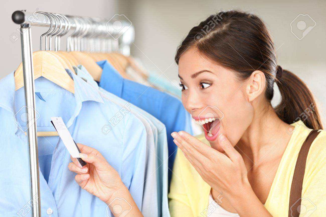 Shopper woman surprised over sale price. Happy Asian shopping woman surprised over rebate prices looking at price tag on clothes. Mixed race Asian chinese / Caucasian young female model. Stock Photo - 13506291