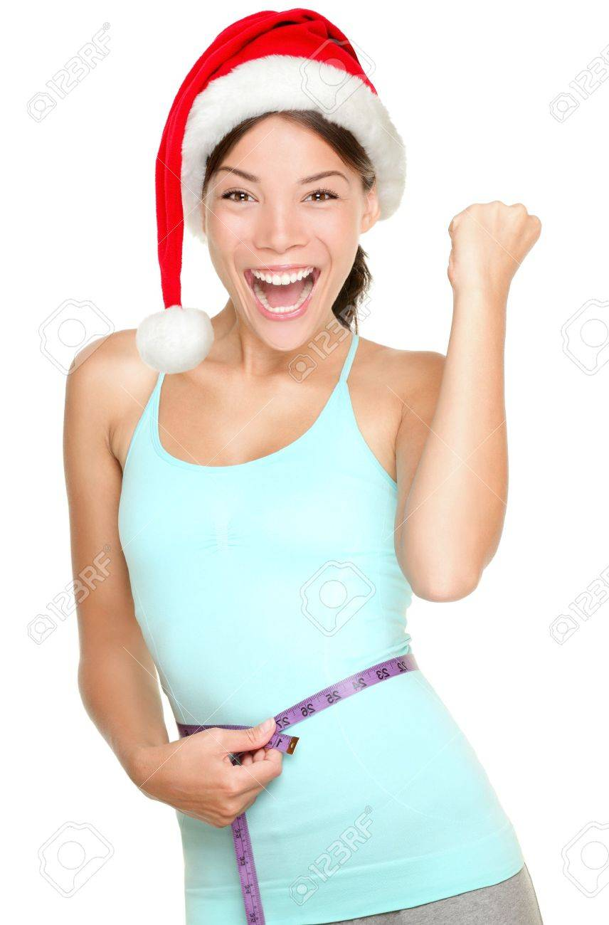 Christmas fitness woman excited about weight loss measuring waist with measuring tape wearing santa hat screaming excited Mixed race fitness model isolated on white - 15717299