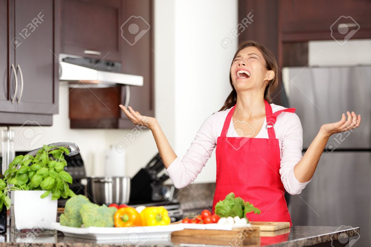 funny cooking image of woman crying and screaming in kitchen stock