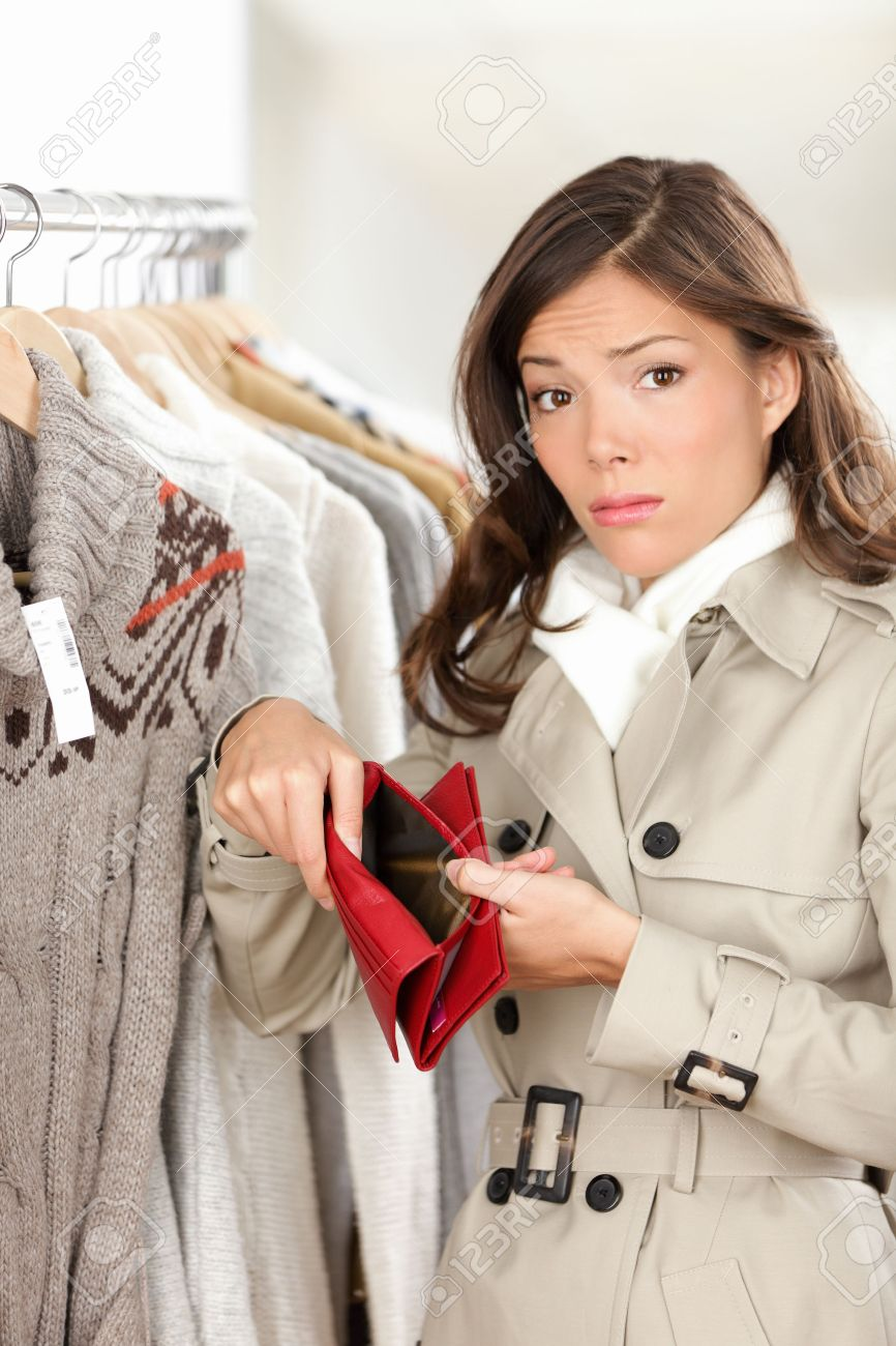 Woman shopper holding empty wallet or purse while shopping in store  Sad young woman looking at camera in clothing shop Standard-Bild - 16637281