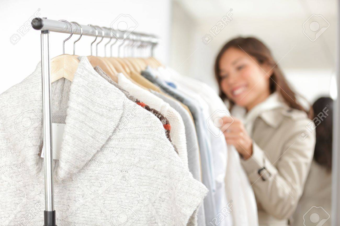 Clothing  Woman shopping clothes in store looking at clothing rack  Focus on winter sweater in foreground Standard-Bild - 16637277