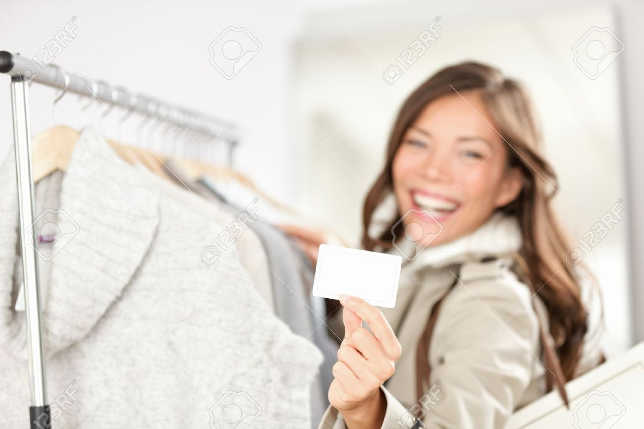 Gift card woman shopping clothes  Happy shopper holding showing gift card or business card in store while shopping for clothing Standard-Bild - 16637275