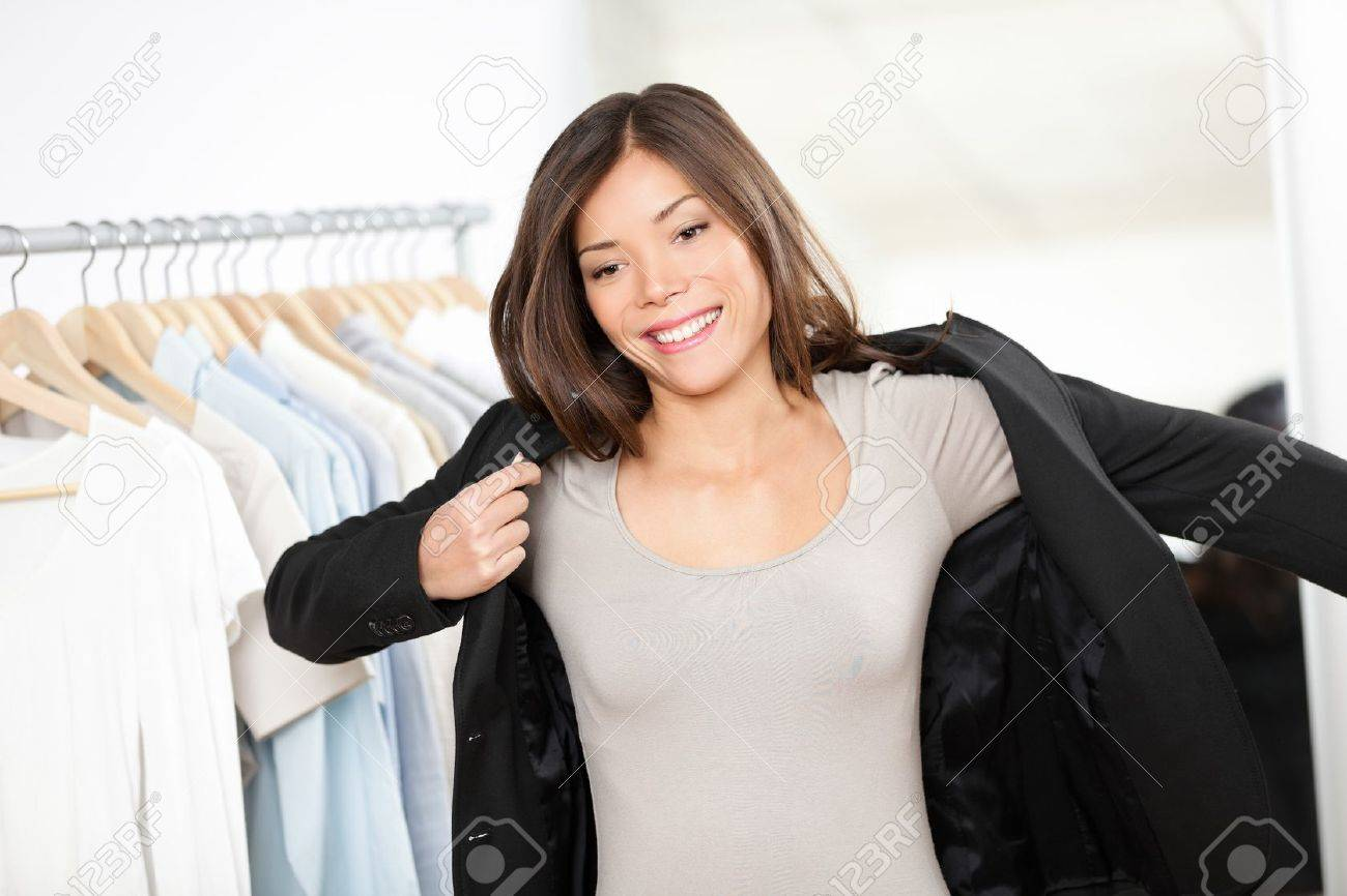 Woman shopping for business suit clothes in clothing store trying on jacket for businesswoman  Beautiful young professional business woman of mixed Asian Chinese   Caucasian ethnicity looking in mirror Standard-Bild - 16637279