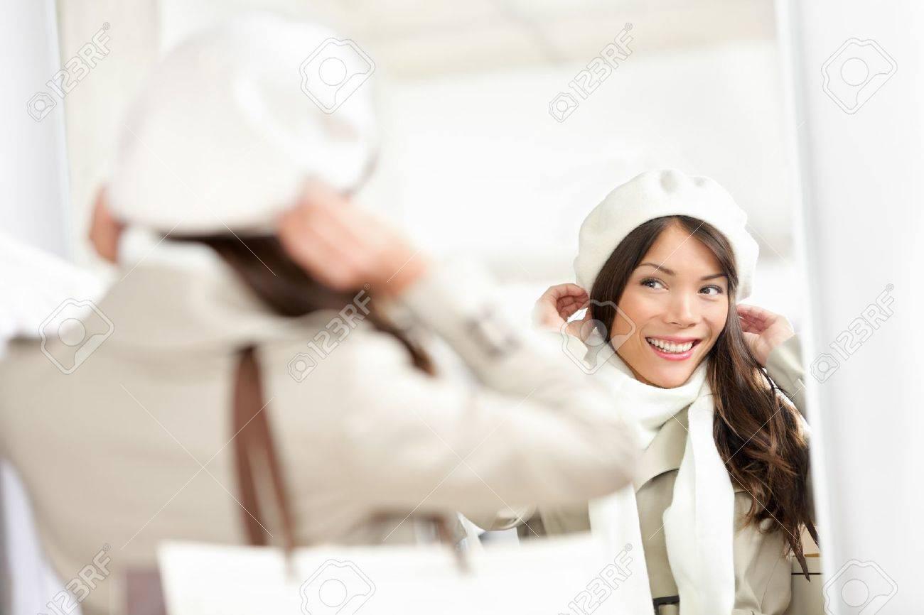 Winter shopping Frau Shopper versucht auf dem Hut in der Kleiderkammer beim Verkauf Multikulturelle Frau schaut im Spiegel Standard-Bild - 16637284