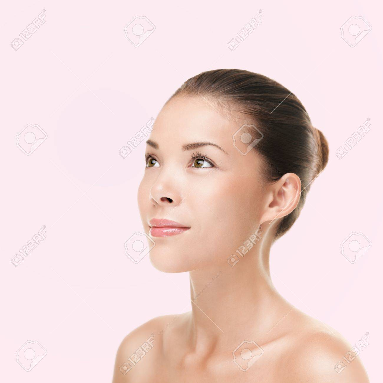 Multiracial ethnic Asian and Caucasian female beauty model looking to the side and up on bright pink background. Standard-Bild - 16663400