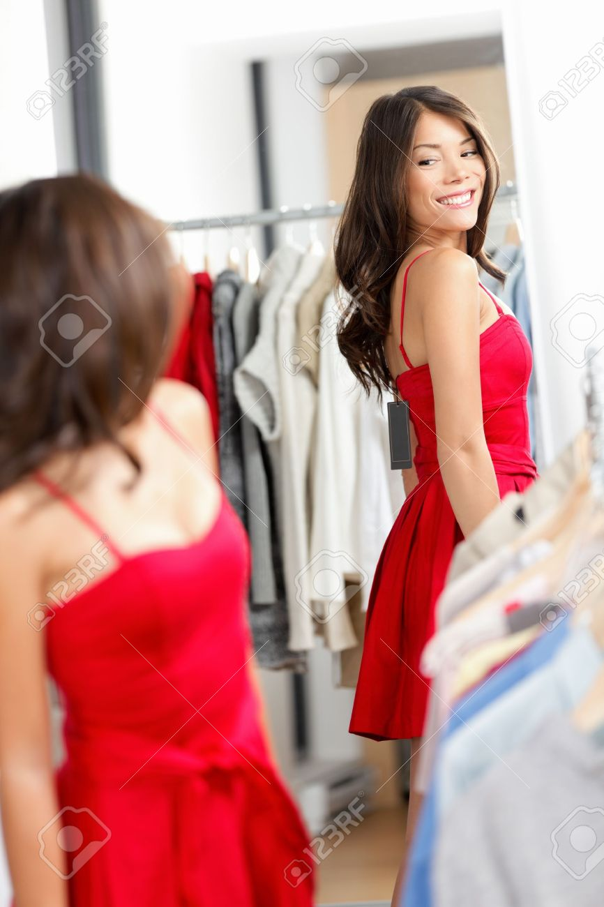Woman shopping looking in mirror trying clothes dress in clothing store. Young beautiful multicultural woman trying on red dress in fitting room. Mixed race Caucasian Asian girl in her twenties. Standard-Bild - 17892535