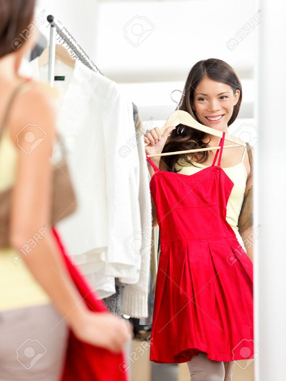 Shopper Frau, die versucht Kleidung Kleid beim Einkaufen in Bekleidungsgeschäft beim Verkauf. Schöne junge multikulturelle Asian / kaukasischen weibliche Modell lächelnd glücklich und fröhlich. Standard-Bild - 17892534