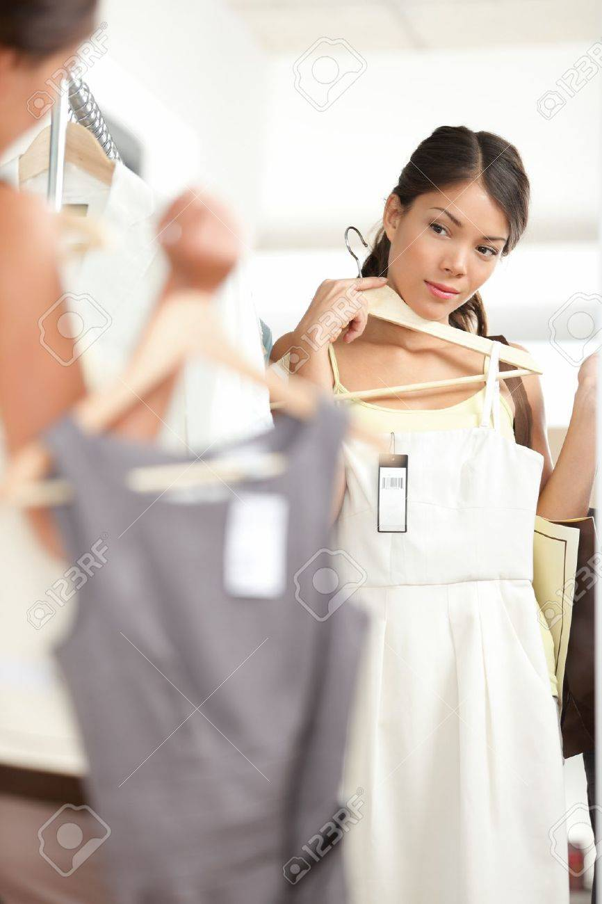 Woman shopping choosing dresses looking in mirror uncertain. Beautiful young multicultural shopper in clothing store. Standard-Bild - 17892533