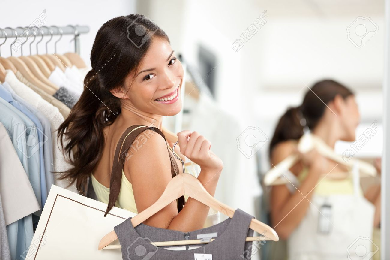 Happy shopping woman in clothing store smiling holding shopping bags and clothes dress. Beautiful Eurasian model inside Standard-Bild - 17892537