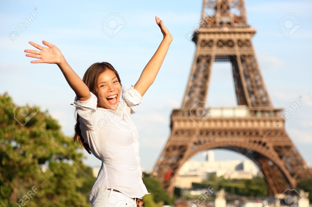 Happy tourist on travel holidays cheering joyful with arms raised up excited at Paris Eiffel Tower Standard-Bild - 20047436