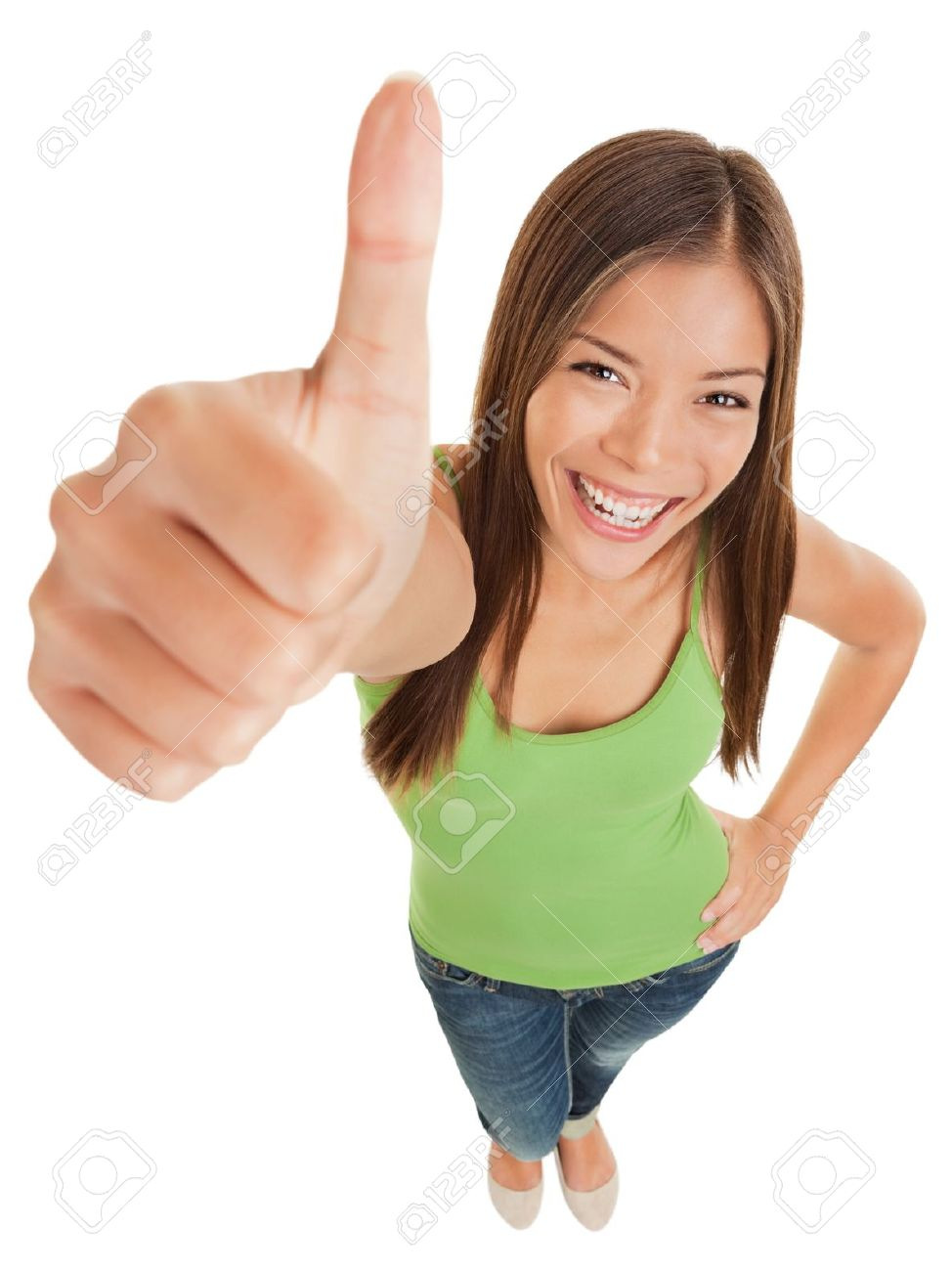 Fun high angle portrait of an attractive vivacious young woman giving a big thumbs up of success and approval isolated on white Standard-Bild - 20047447