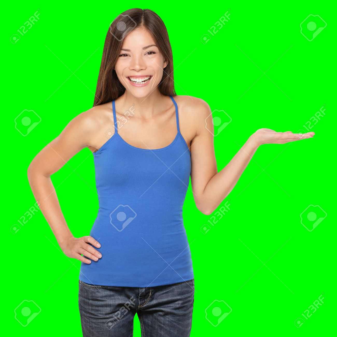 Woman showing your product or message smiling happy Isolated on green screen chroma key background. Beautiful multi-racial girl in blue tank top showing open hand palm. Standard-Bild - 39266670