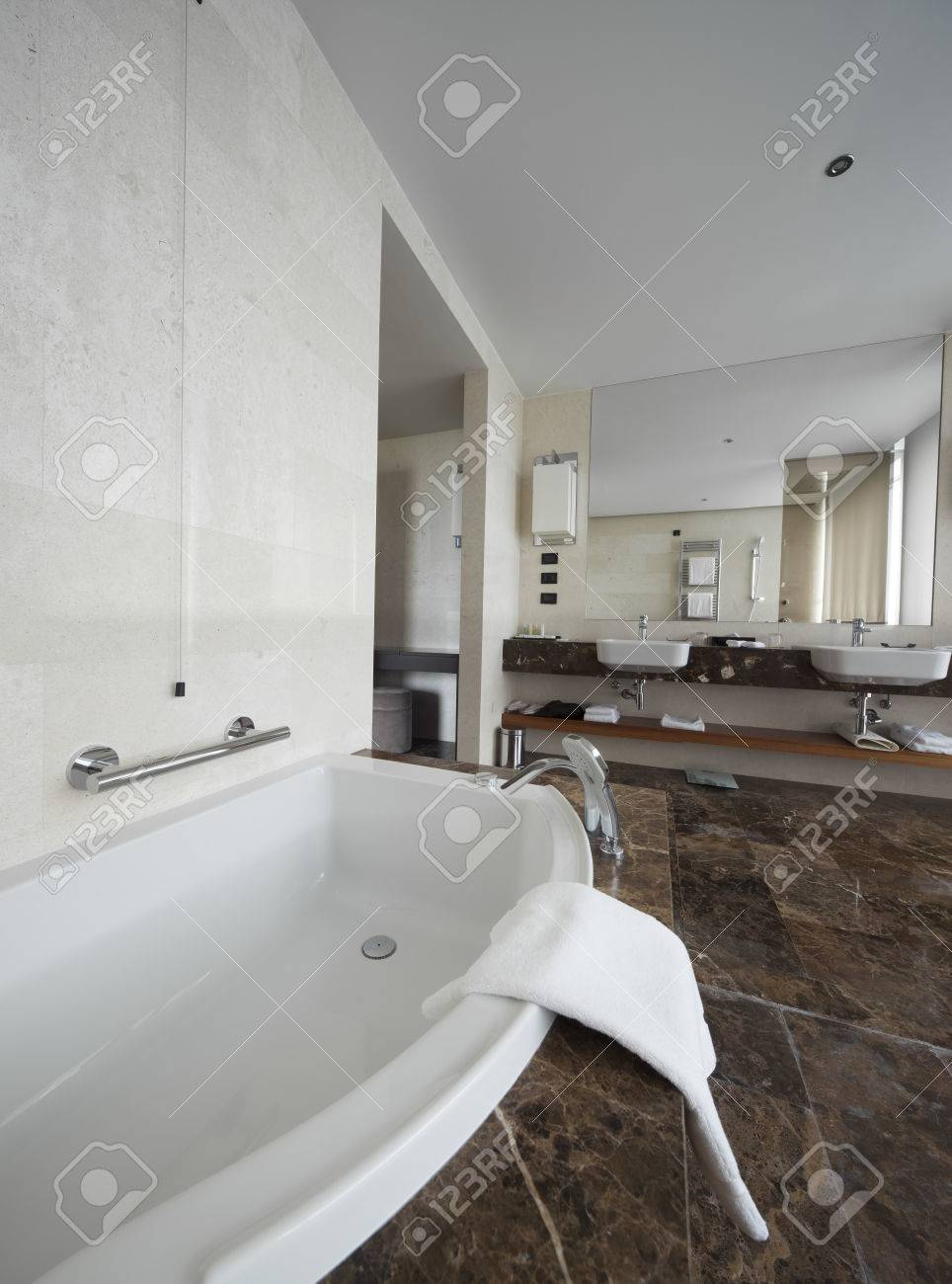 Intérieur salle de bains moderne avec lavabo double et de grands miroirs,  baignoire, tuiles, fenêtre de vue et les serviettes.