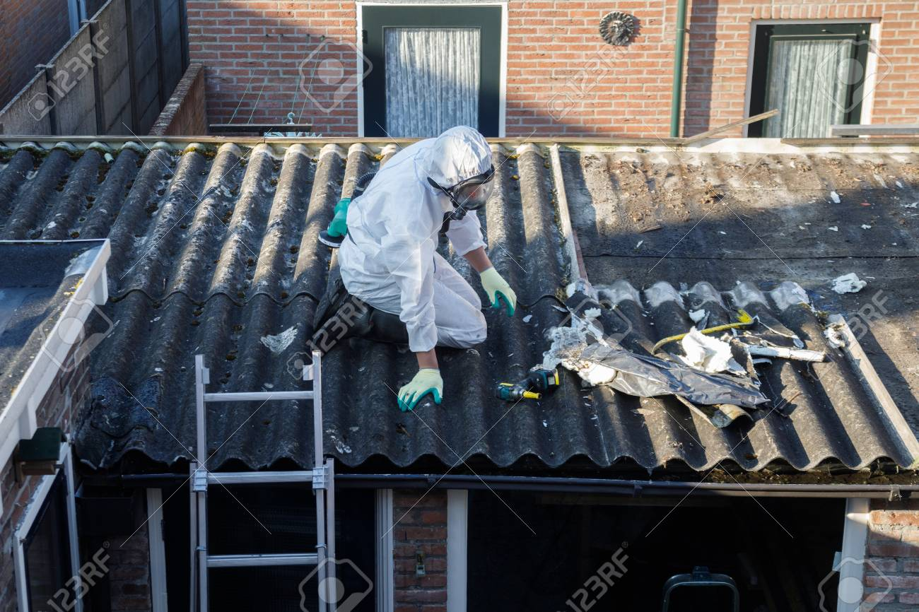 Professional asbestos removal. Men in protective suits are removing asbestos cement corrugated roofing - 122497040