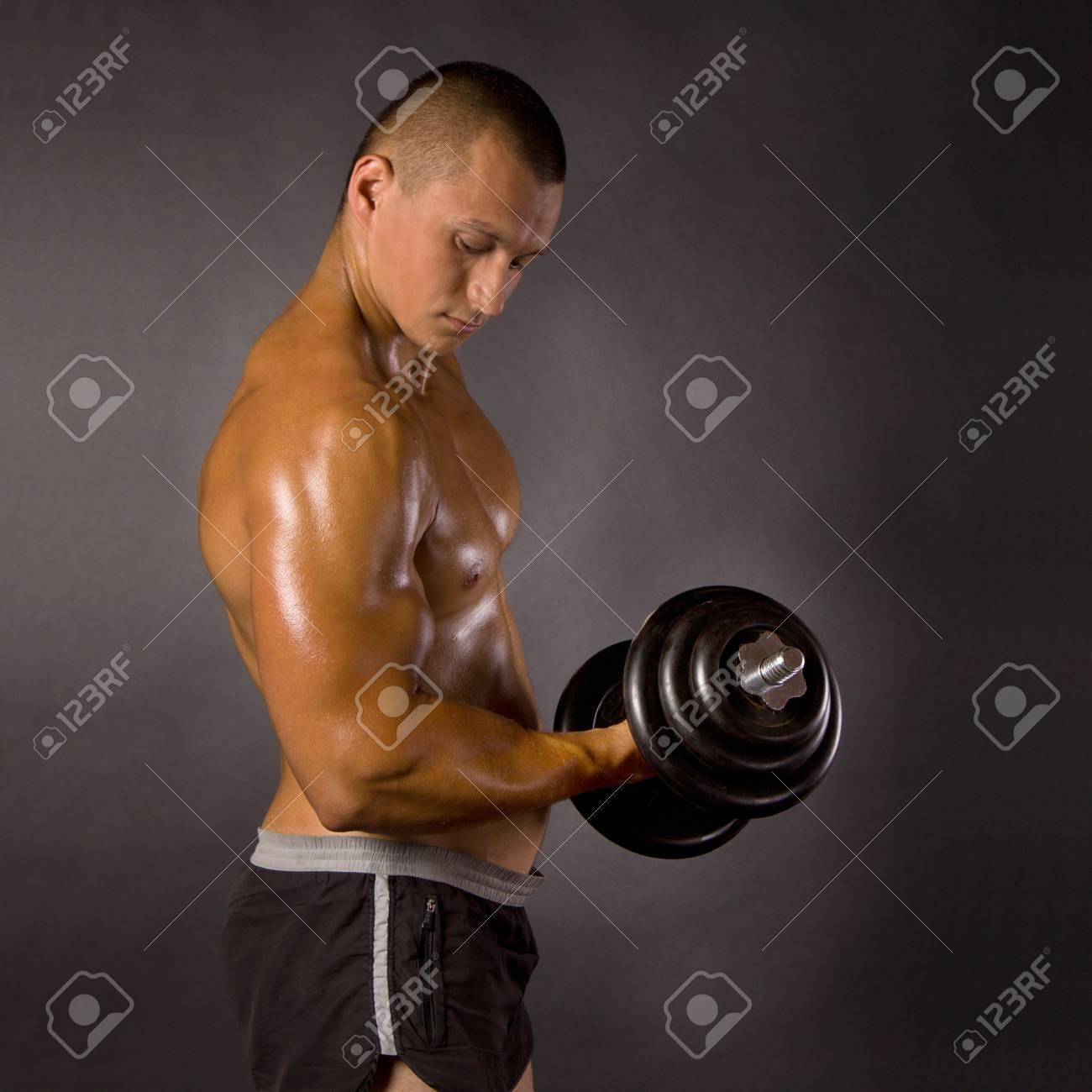 Muscled male bodybuilderweight, dumbbell, raise, swing Stock Photo - 13801877