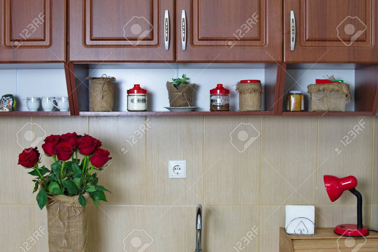 Mobili da cucina in legno e ripiano e bouquet di rose rosse primo piano