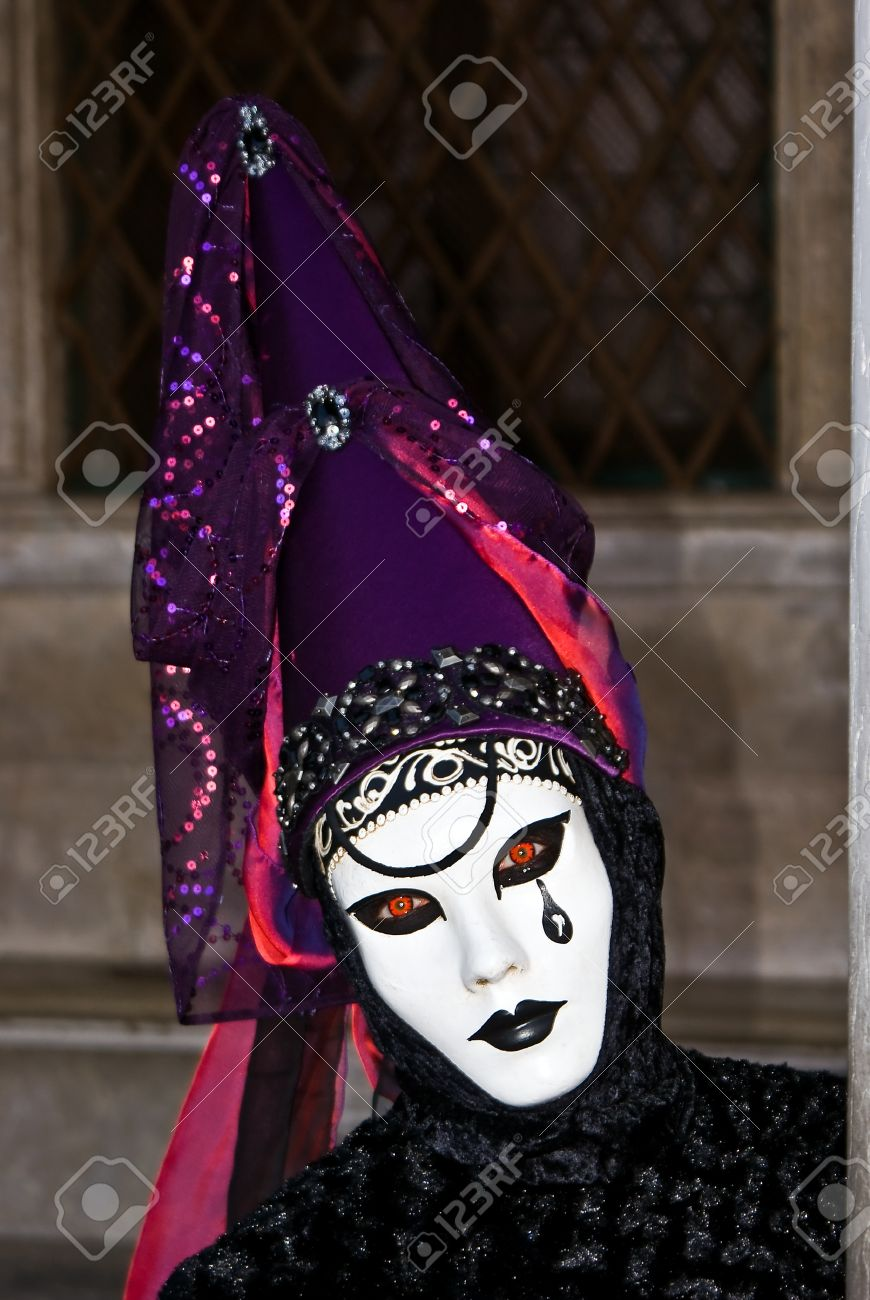 Carnival mask in a black and purple costume, Venice in Italy Stock Photo - 13511946