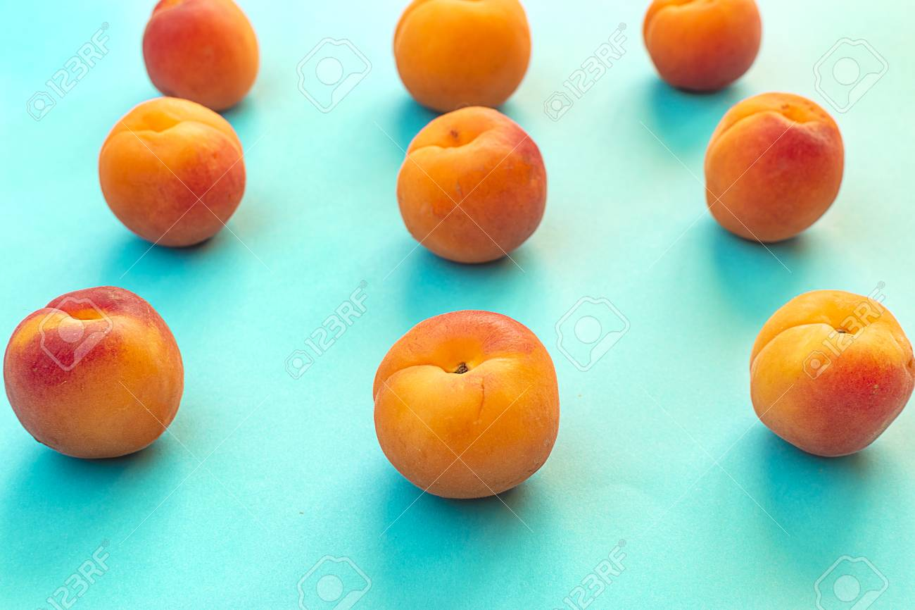 Symmetry of apricots with blue background. Set of apricots placed symmetrically. - 125503706