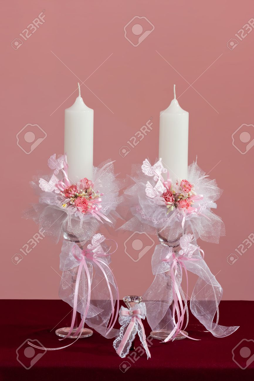baby girl christening candles with artificial pink flowers and