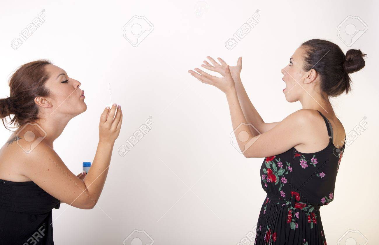 Portrait of a two beautiful sexy women blowing bubbles. Stock Photo - 16238573