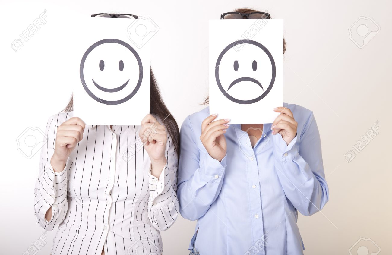 Portrait of a two young women holding smiley and sad smiley face. Stock Photo - 16238575