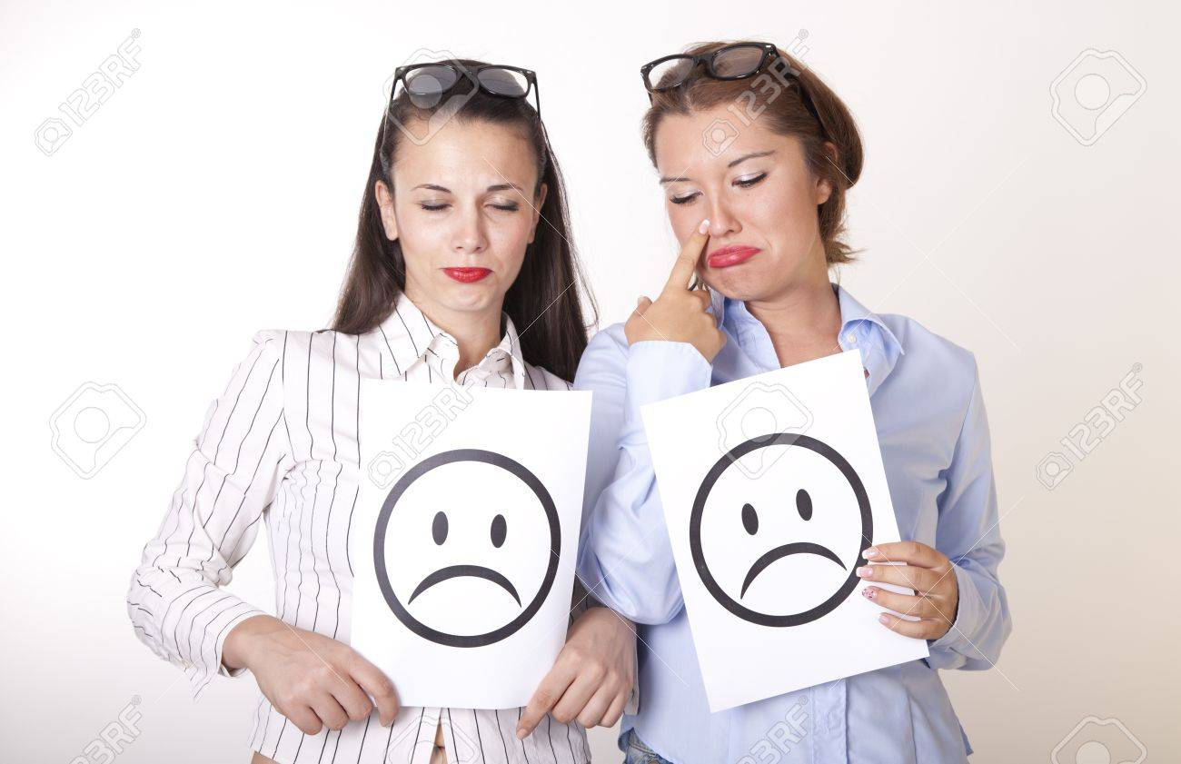 Portrait of a two young beautiful women holding sad smiley faces. Stock Photo - 16238570