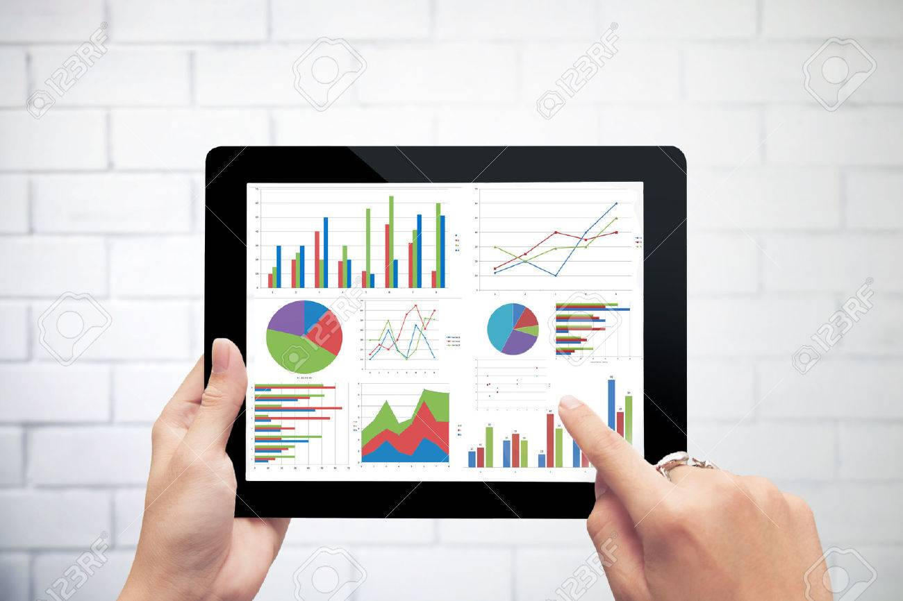 Close up hand holding digital tablet with analyzing graph against close up hand holding digital tablet with analyzing graph against white wall background stock photo ccuart Image collections