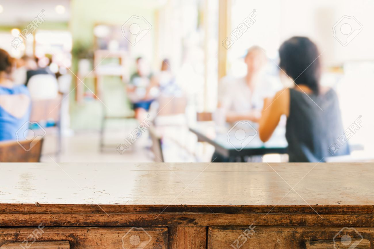 Empty wood table and blurred living room background stock photo - Empty Wooden Table And Blurred People In Cafe Background Product Display Montage Stock Photo