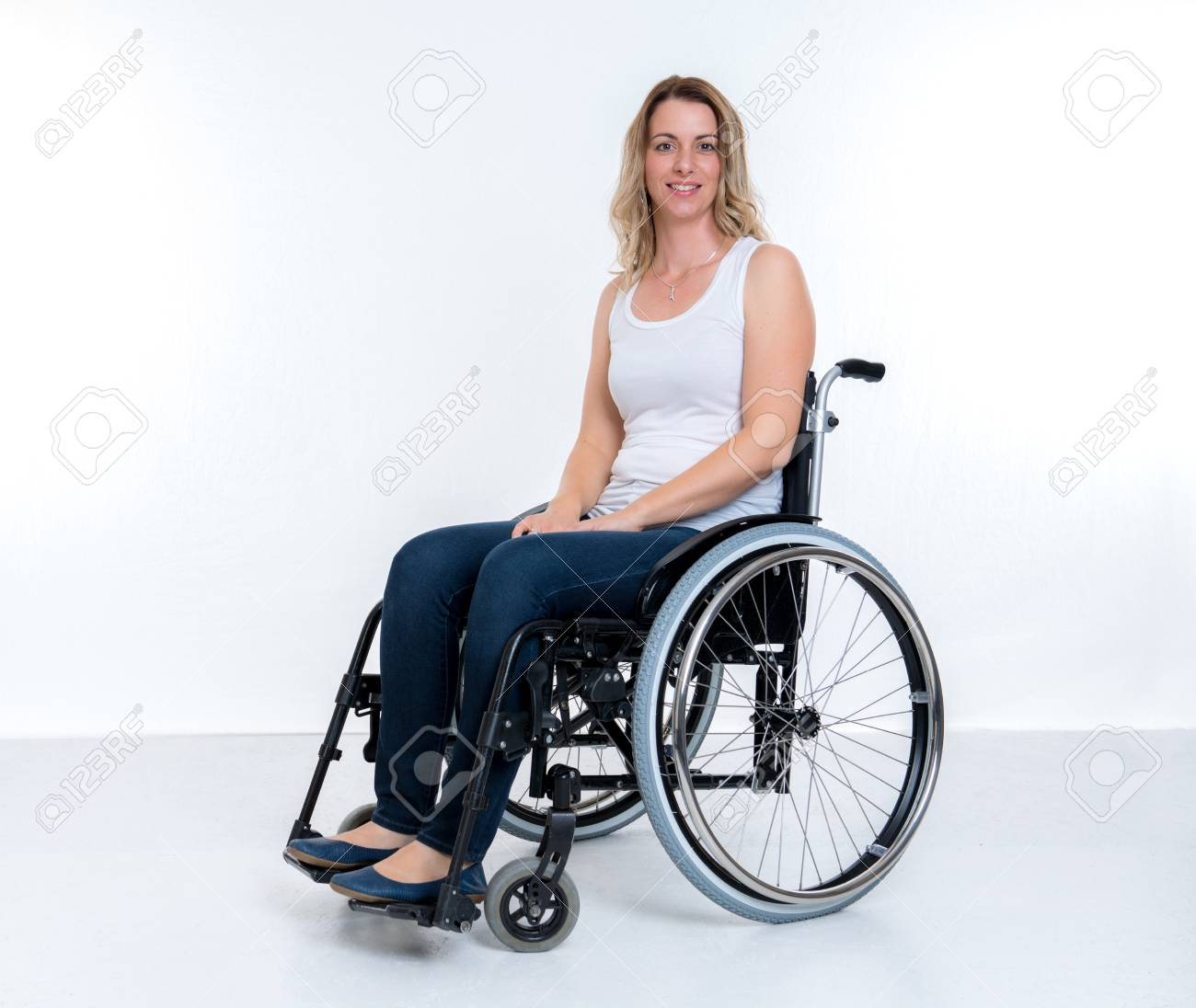 young disabled woman in wheelchair infront of white background stock